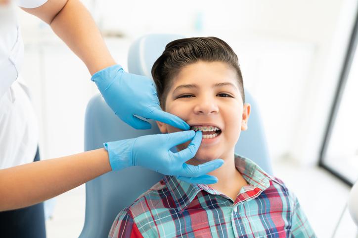 Female orthodontist examining cute boy wearing braces